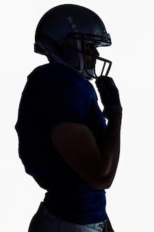 Vista lateral da silhueta jogador de futebol americano vestindo capacete