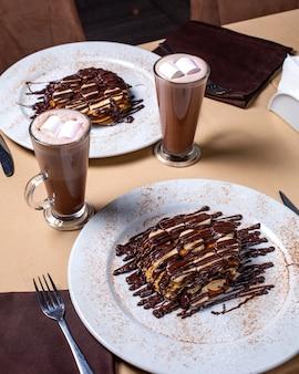 Vista lateral da sobremesa com bananas cobertas com chocolate e servido com cacau com marshmallow em copo em cima da mesa
