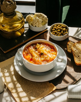 Vista lateral da sopa com couve-flor cenoura e batatas em uma placa de madeira