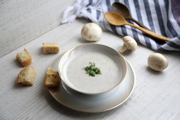 Vista lateral da sopa creme de cogumelos em tigela branca