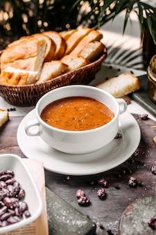 Vista lateral da sopa de creme de lentilha em uma tigela branca