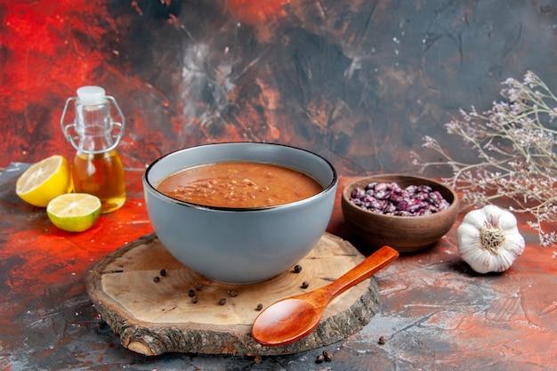 Vista lateral da sopa de tomate com colher na bandeja de madeira, frasco de óleo de feijão e tomate com alho e limão na mesa de cores misturadas