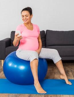 Vista lateral da sorridente mulher grávida em casa treinando com bola e usando smartphone