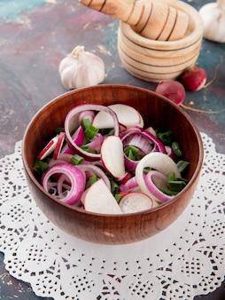 Vista lateral da tigela de salada de legumes com rabanete de cebola e cebolinha no guardanapo de papel com alho no fundo marrom