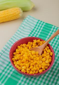 Vista lateral da tigela de sementes de milho com colher no pano e espigas de milho na mesa branca