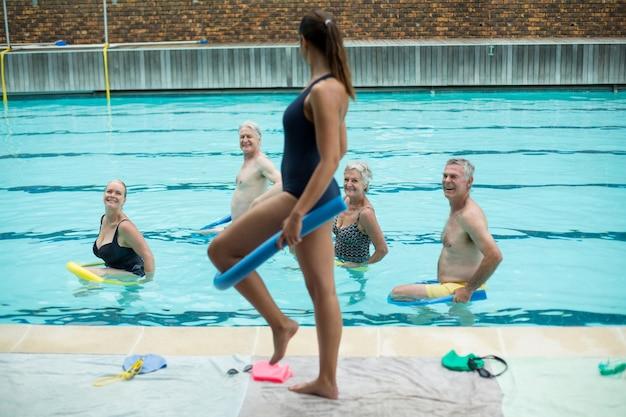 Vista lateral da treinadora demonstrando o uso de macarrão de piscina