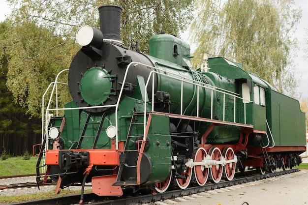 Vista lateral da velha locomotiva a vapor verde.