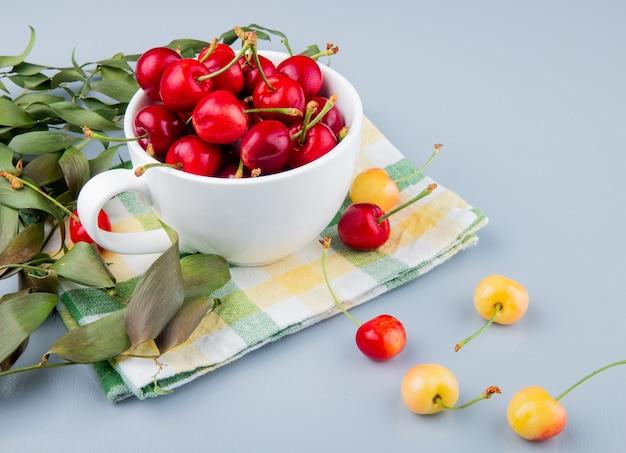 Vista lateral da xícara cheia de cerejas vermelhas no lado esquerdo e mesa branca decorada com folhas