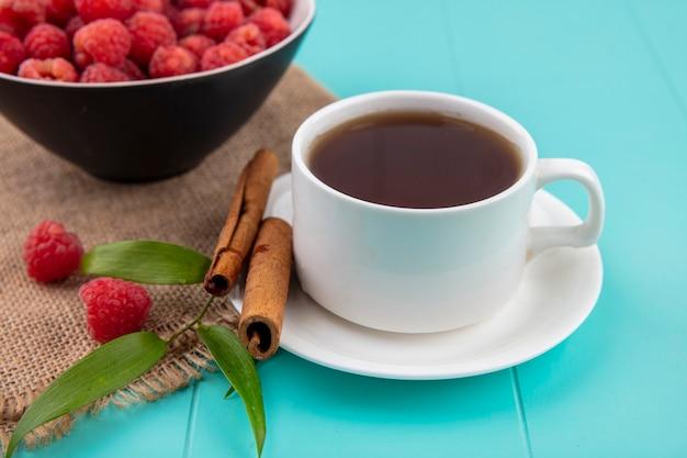 Vista lateral da xícara de chá e canela em saucer com tigela de framboesa e folhas de saco na superfície azul