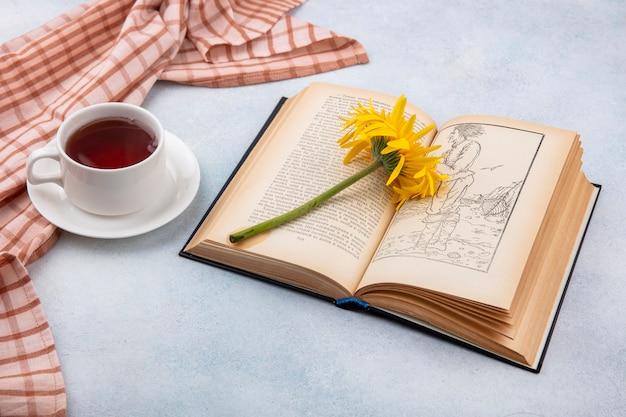 Vista lateral da xícara de chá no pano xadrez e flor no livro aberto na superfície branca