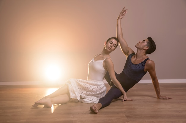 Vista lateral, dançarinos balé, sentando, pose