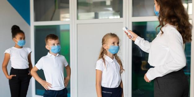 Vista lateral das crianças de volta à escola em época de pandemia