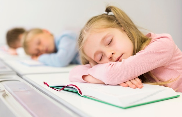 Vista lateral das crianças dormindo em suas mesas