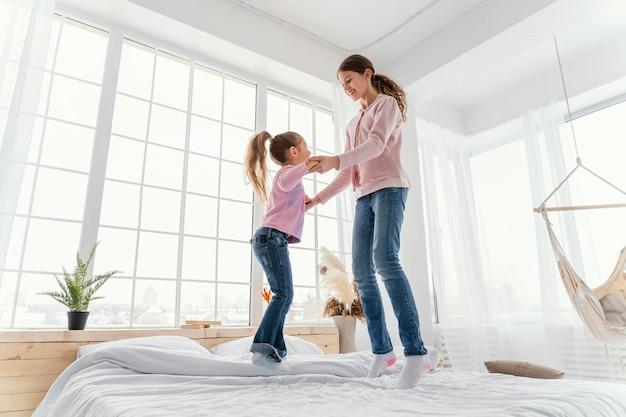 Vista lateral das irmãzinhas pulando na cama juntas