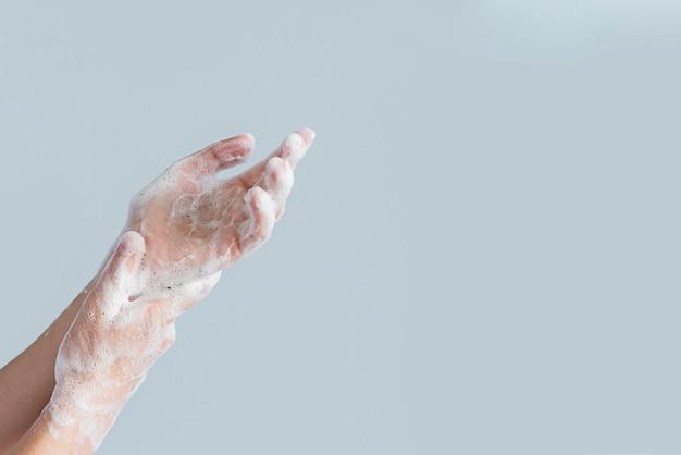 Vista lateral das mãos cobertas de espuma de sabão