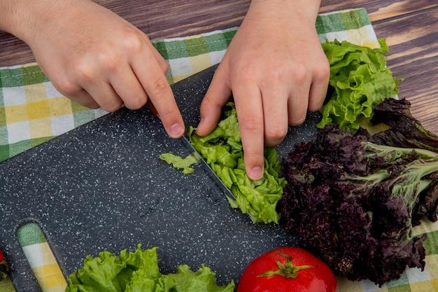 Vista lateral das mãos cortando alface com faca manjericão na tábua e tomate no pano e superfície de madeira