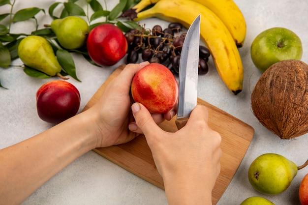 Vista lateral das mãos cortando pêssego com faca na tábua e uva pêra coco banana maçã com folhas no fundo branco