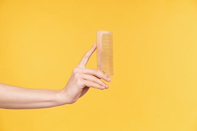 Vista lateral das mãos da jovem mulher bem cuidada, mantendo-se em pé de madeira enquanto vai pentear o cabelo, isolado sobre fundo laranja. conceito de cuidados com os cabelos e mãos humanas