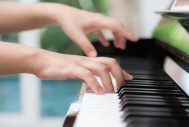 Vista lateral das mãos da mulher que jogam o piano