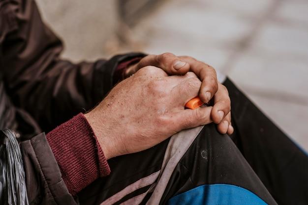 Vista lateral das mãos de um sem-teto