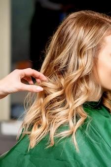 Vista lateral das mãos de uma cabeleireira estilizando o cabelo de uma mulher loira em um salão de beleza