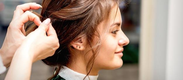 Vista lateral das mãos do cabeleireiro estilizando o cabelo da bela jovem morena caucasiana em um salão de beleza