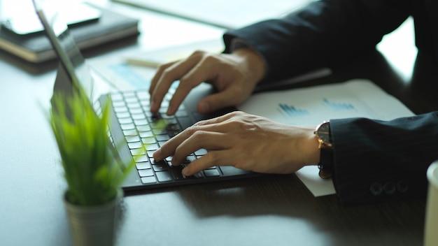 Vista lateral das mãos do empresário digitando no teclado do tablet na mesa do escritório
