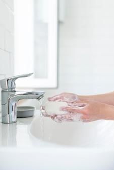 Vista lateral das mãos lavando com barra de sabão