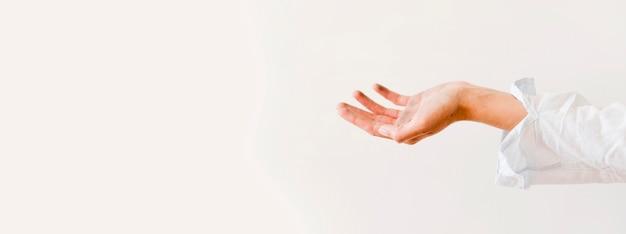 Vista lateral das mãos pedindo doação de alimentos com espaço de cópia
