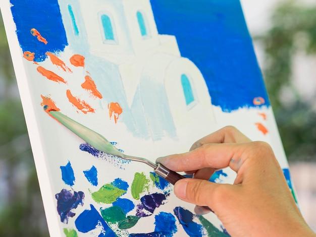 Vista lateral das mãos pintando usando a ferramenta