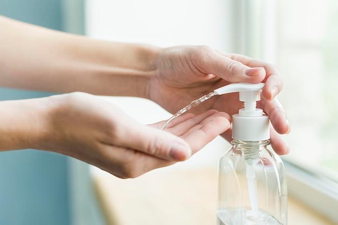 Vista lateral das mãos usando gel desinfetante para as mãos