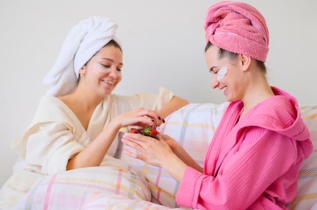 Vista lateral das mulheres, aproveitando o dia do spa em casa e comer frutas