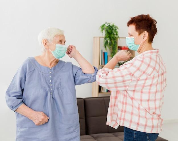 Vista lateral das mulheres mais velhas, cumprimentando-se em casa