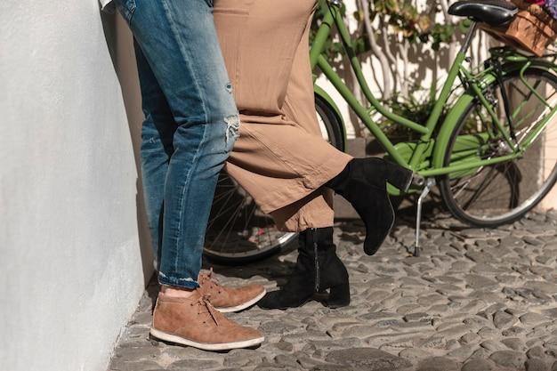 Vista lateral das pernas do casal com bicicleta