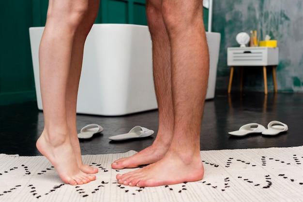 Vista lateral das pernas do casal com chinelos