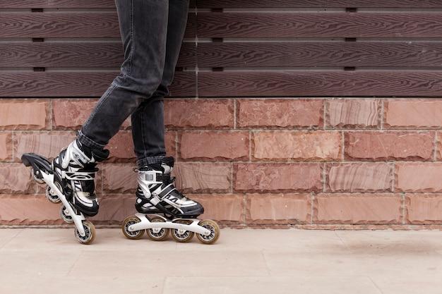 Vista lateral das pernas usando patins com espaço de cópia