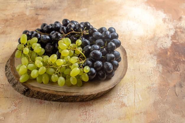 Vista lateral das uvas - as apetitosas uvas pretas e verdes na placa de madeira