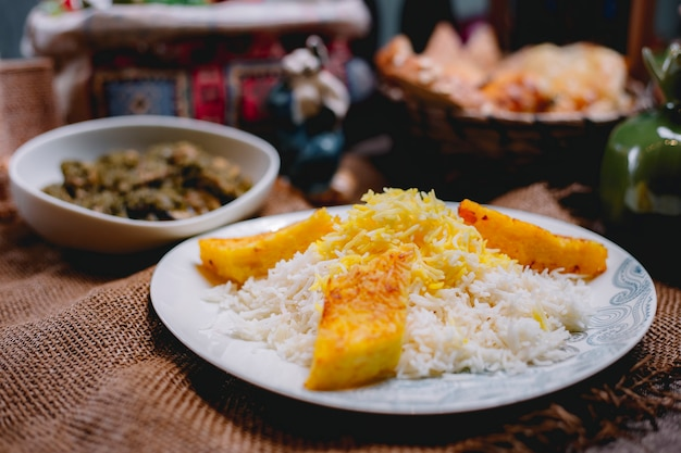 Vista lateral de abóbora com arroz em um prato branco