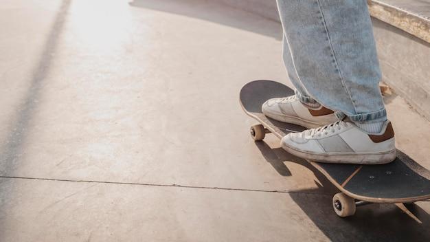 Vista lateral de adolescente no skatepark com espaço de cópia