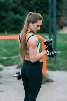 Vista lateral, de, ajustar, mulher, levantamento, dumbbell, para, braços treinam, parque