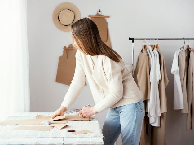 Vista lateral de alfaiate feminina no estúdio com roupas