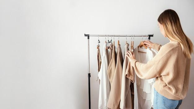 Vista lateral de alfaiate feminina verificando roupas em cabides com espaço de cópia