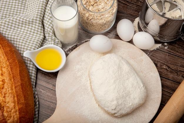 Vista lateral de alimentos como manteiga derretida, pão de leite ovos com flocos de aveia e massa polvilhada com farinha na tábua sobre fundo de madeira