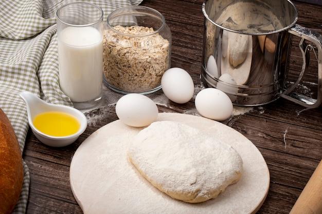 Vista lateral de alimentos como ovo de leite manteiga derretida com flocos de aveia e massa polvilhada com farinha na tábua sobre fundo de madeira