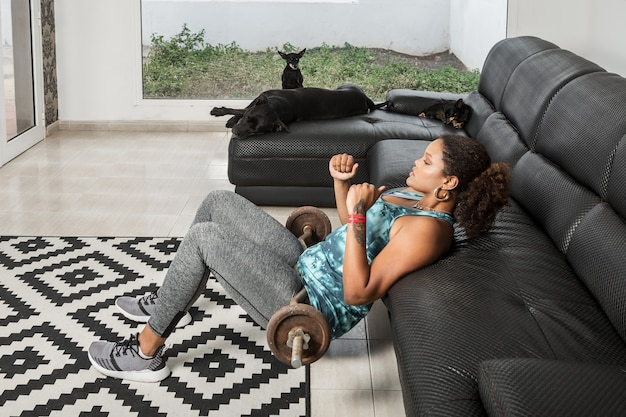 Vista lateral de alto ângulo de uma atleta afro-americana focada em roupas esportivas, fazendo exercícios de ponte e bombeando os músculos das nádegas enquanto pratica com barra na sala com cães