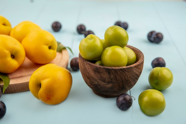 Vista lateral de ameixas de cereja verdes em uma tigela de madeira com pêssegos amarelos isolados em uma placa de cozinha de madeira em um fundo azul