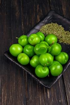 Vista lateral de ameixas verdes azedas com hortelã-pimenta seca em uma bandeja preta na mesa de madeira escura