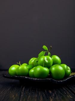 Vista lateral de ameixas verdes azedas com hortelã-pimenta seca em uma bandeja preta na mesa escura