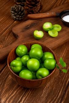 Vista lateral de ameixas verdes azedas em uma tigela de madeira e ameixas fatiadas com faca de cozinha e sal em um pires na mesa rústica