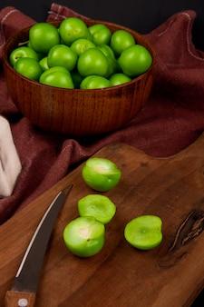 Vista lateral de ameixas verdes azedas em uma tigela de madeira e fatias de ameixas verdes com uma faca de cozinha em uma placa de madeira na mesa de tecido vermelho escuro